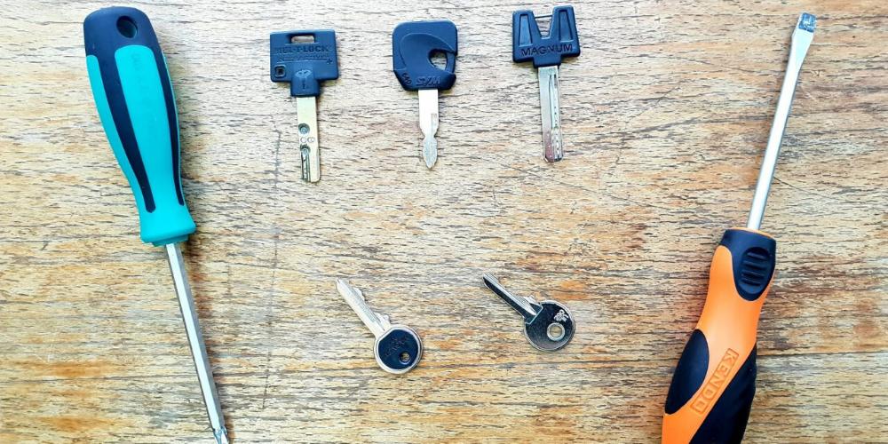 5 מפתחות שחורים מונחים על יד זוג מברגים על רקע עץ ווינטג' - תמונת רקע המנעולן שלך.